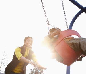 Mother pushing child on swingset