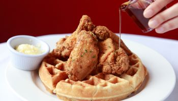 pouring syrup on fried chicken and waffles on restaurant table with butter