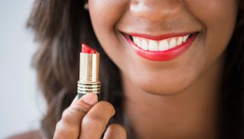 Black woman holding lipstick