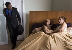 Businessman walking into bedroom and finding couple in bed