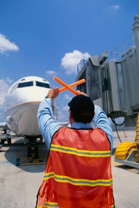 Ground crew directing plane to the gate jetway