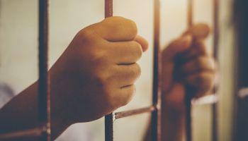 Cropped Hands Of Prisoner In Jail