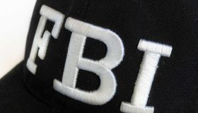 Close up of the FBI logo on a black cap. The text stands for...