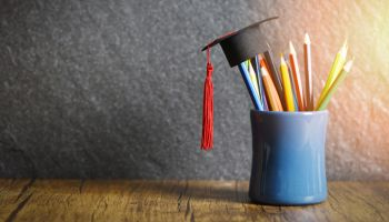 Close-Up Of Multi Colored Pencils With Mortarboard In Desk Organizer On Table
