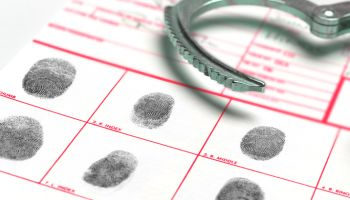 Looking At Finger And Thumb Prints at Police Station, with Handcuffs